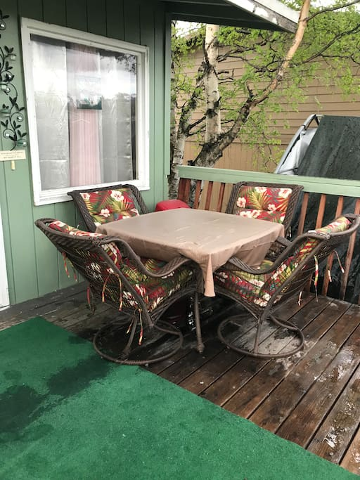 Back porch with table and barbecue grill.