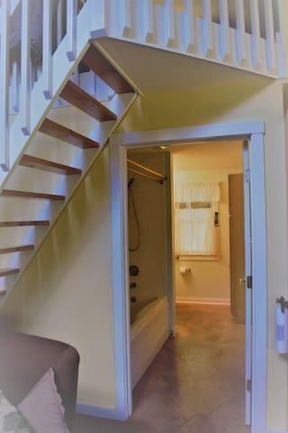bathroom entrance under stairs to loft (additional sleeping or yoga/meditation space)