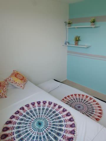Habitación con dos camas sencillas y aire acondicionado