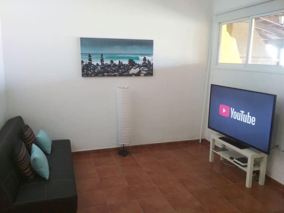 Salón con un sofá cama de cuatro plazas, y  smart TV con entrada USB y HDMI e internet (Wi-Fi)