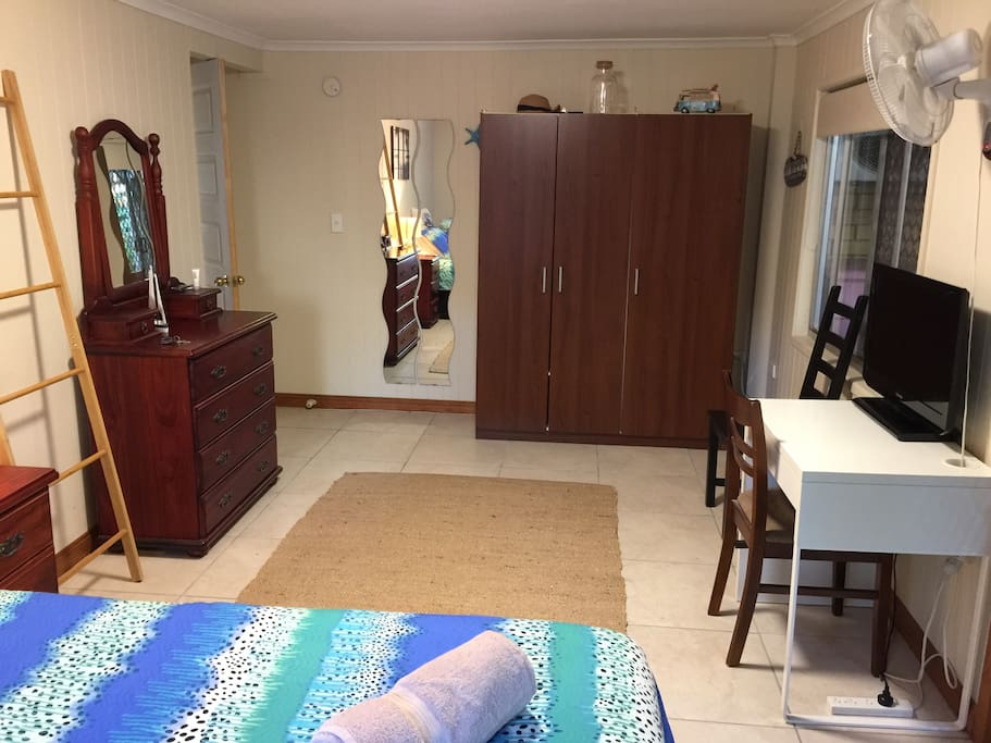 1st bedroom wardrobe, set of drawers/mirror and desk/TV.  One Queen size bed.