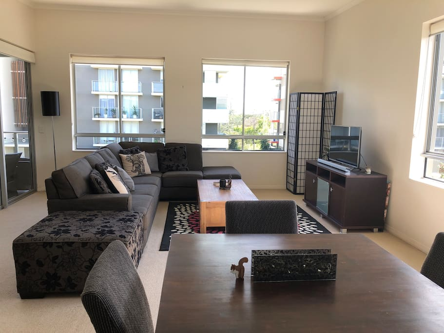 Open space living area with smart tv, large comfortable couch, dining area and balcony just to the left. You are welcome to use the guest profile on my Netflix account.