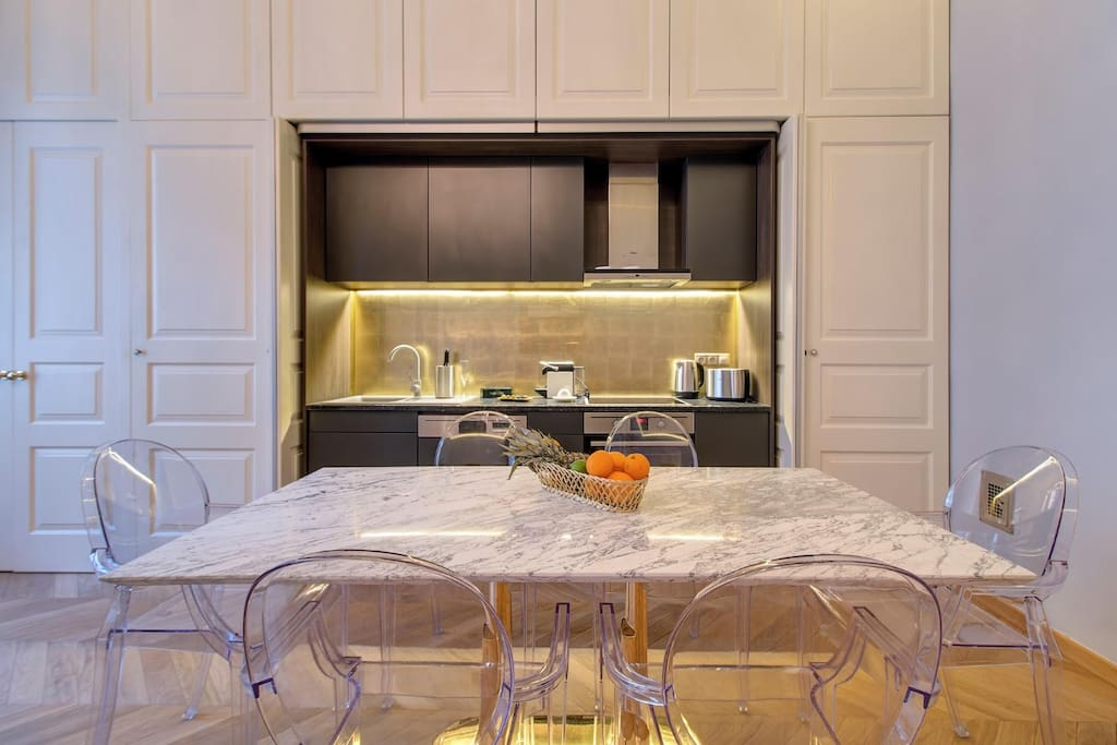 Integrated modern kitchen with built in appliances and a grand Calacata marble table.