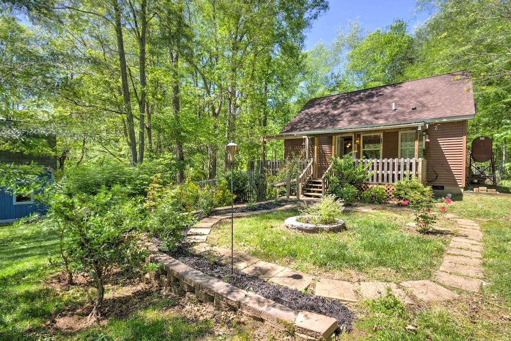 The home features a covered back deck overlooking a fenced-in yard with a hammock, swing and small creek.
