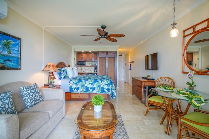 King bed, with view to ocean, mounted TV, table and chairs, full pull out sofa bed, AC, kitchenette, and ceiling fan.
