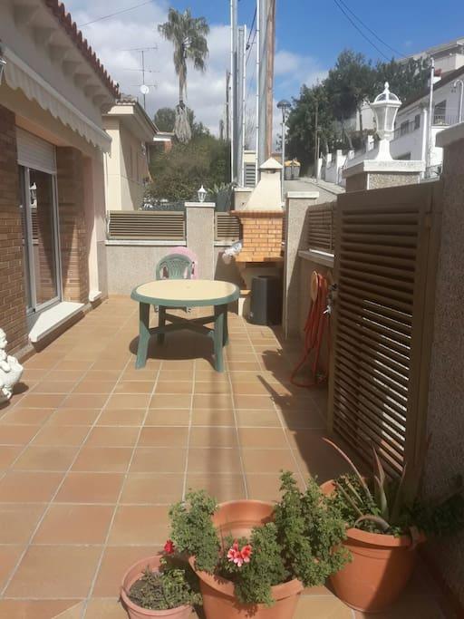 Entrada a casa por una terraza con Barbacoa y abertura a la cocina