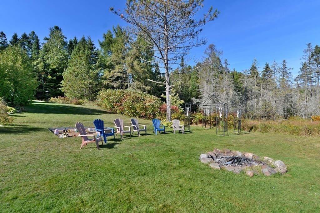 Endroit pour faire un feu avec bois et chaises disponibles. Fire pit with wood and chairs available.