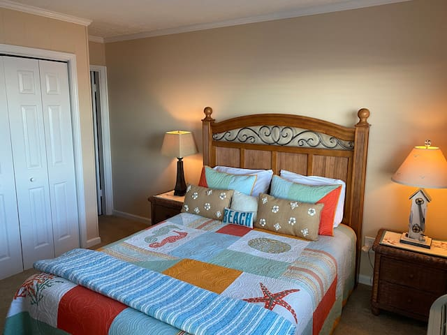 Master bedroom with a queen size bed, ocean front windows and a private door to the balcony. The bedroom has a private bathroom with shower.