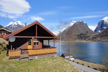 Cabin by the fjord under the glacier in Fjærland
