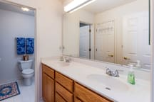 Full bathroom: Double vanity & linen closet.