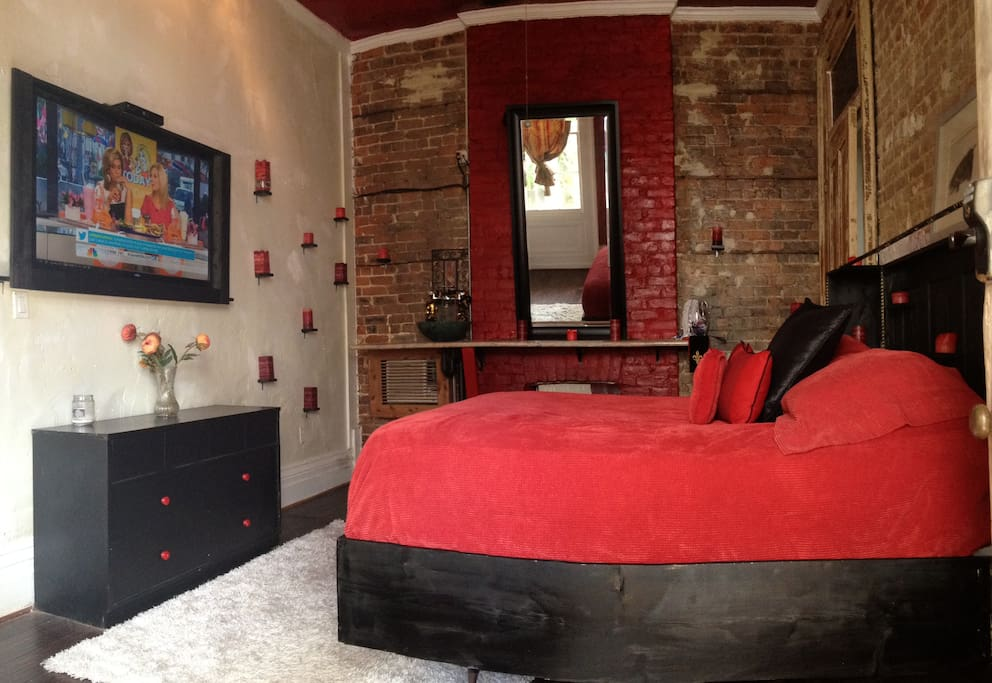 Red Room has big screen Tv, heating and cooling, exposed brick, dim lighting, bath with walk in shower and double vanity.