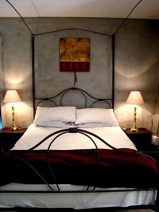 Romantic bedroom with wrought iron double bed