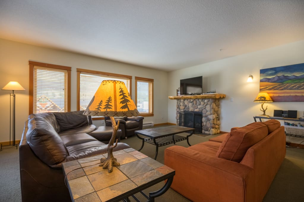 Living room with TV, cosy fireplace, comfortable sofas, local artwork and views of Mount Lady Macdonald, Grotto Mountain.