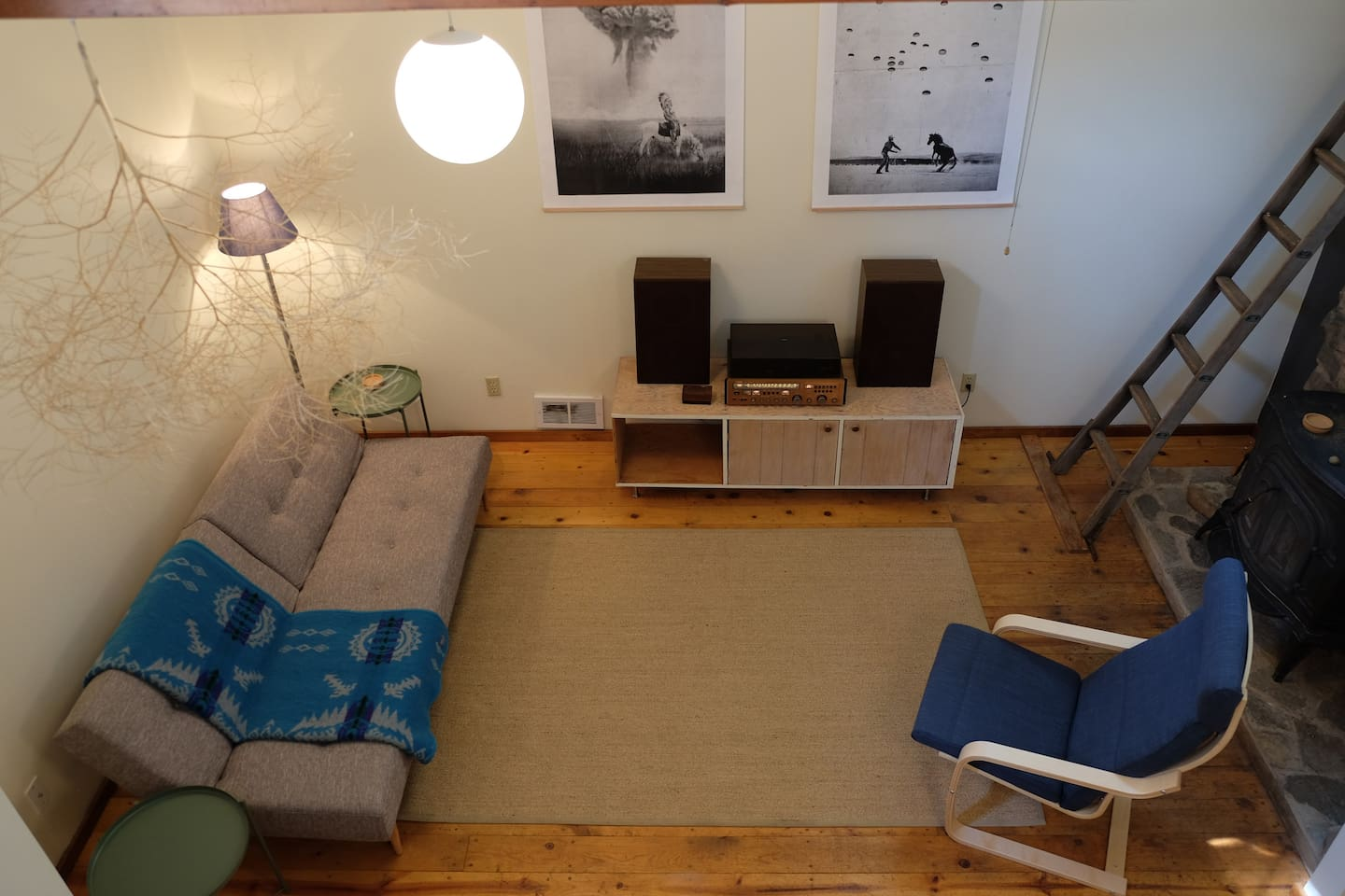 Roomy central living space with a fold out couch, table for 8, a fireplace and a record player.