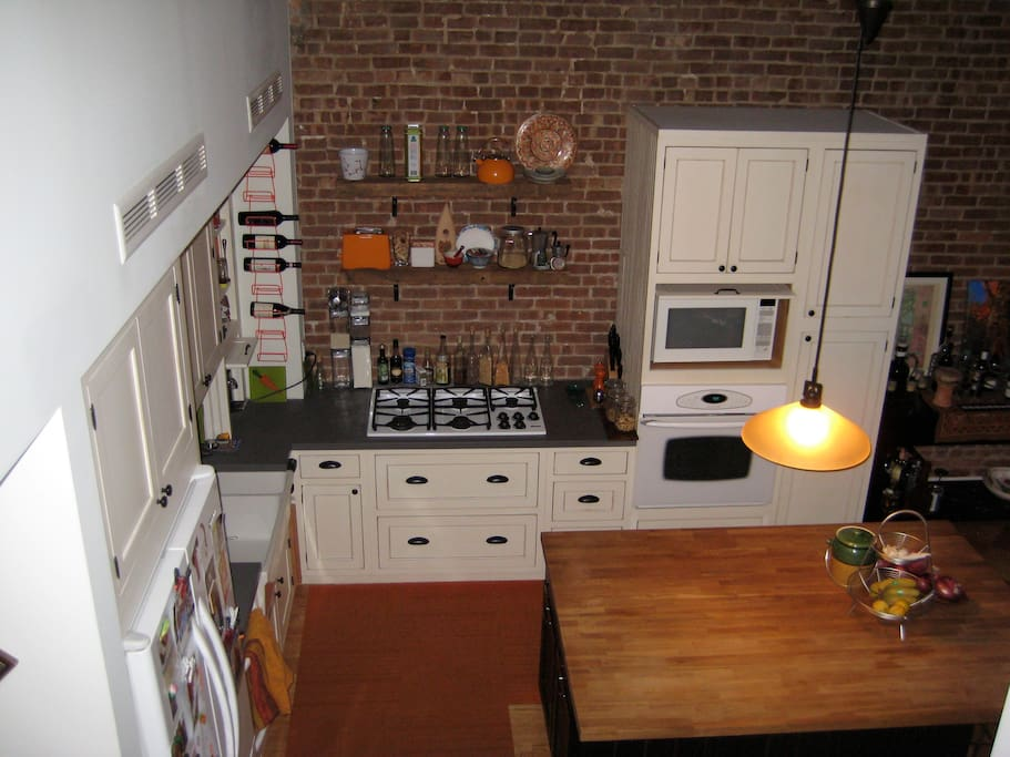 Kitchen - view from the stairs to the penthouse - w/ gas stovetop, dishwasher, oven, and microwave.