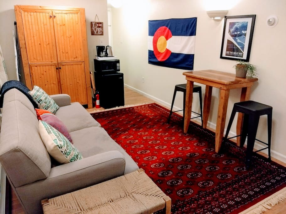 Our bright, cozy living area of our Colorado-themed guest suit features vintage post cards of local attractions and art by local artists.