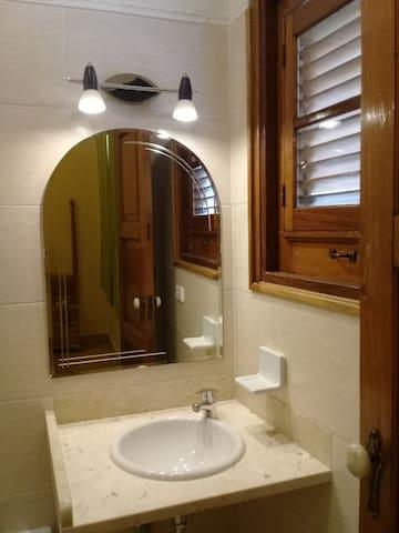 baño con buena iluminación y ventanas al exterior