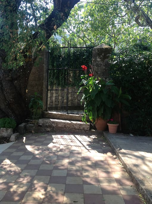 The entrance and original gate. Very very old. Almost as old as the almond tree there.