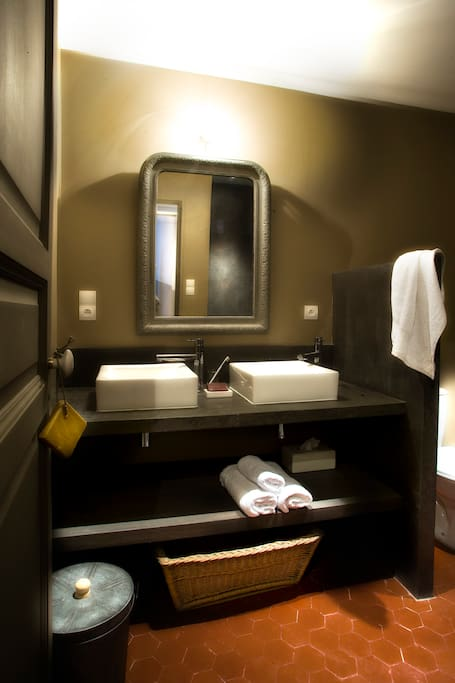 la salle de bain avec une vaste douche a l'italienne en béton cire.