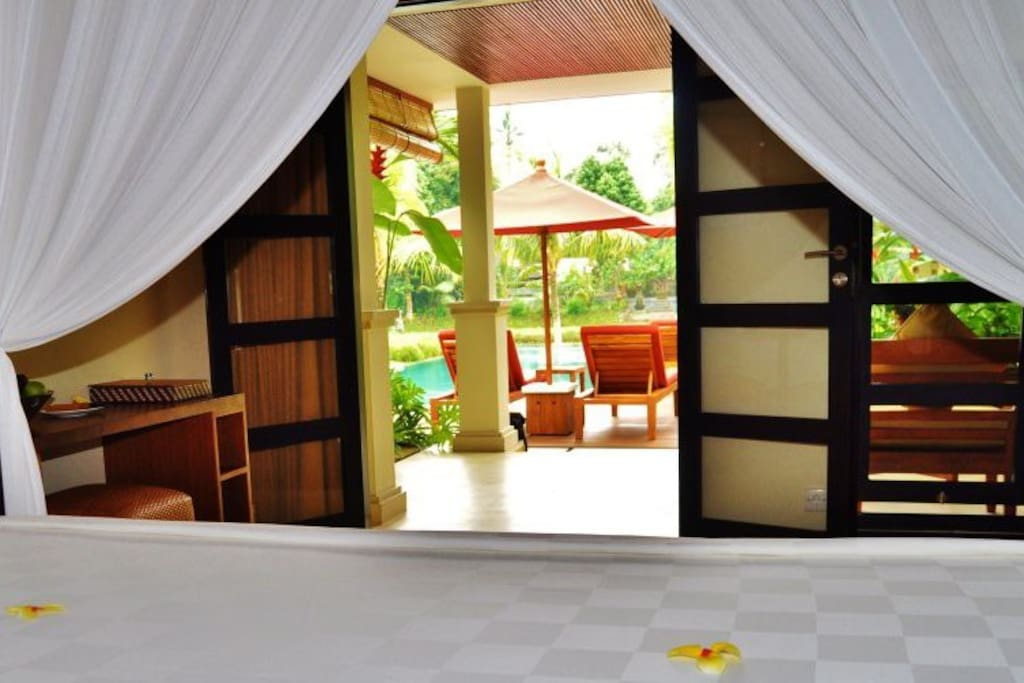 This room has got a poster bed and a pool/tropical garden view. The rice paddies begin where the pool ends.