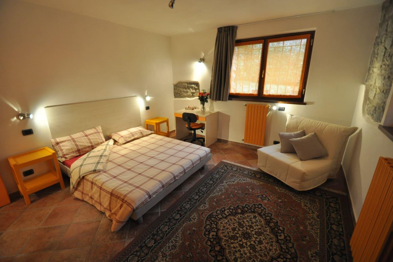 Una camera accogliente con vista sul giardino - A comfortable room with a garden view