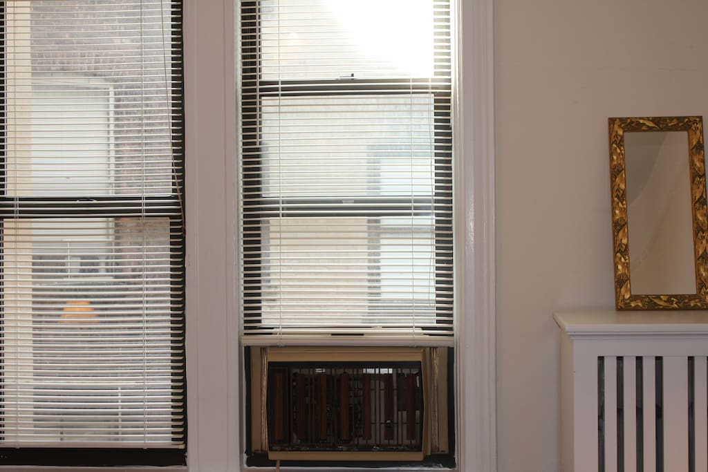 There are two windows in the bedroom, with lots of natural light, and a window unit air conditioner.