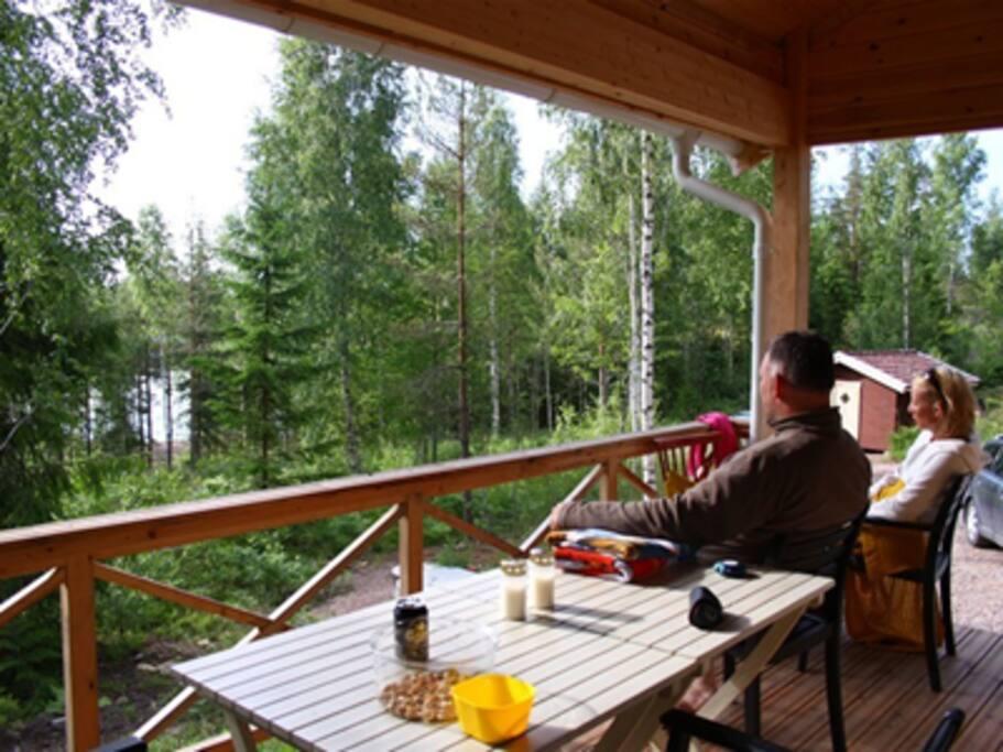utsikt från verandan, sjön syns svagt mellan träden