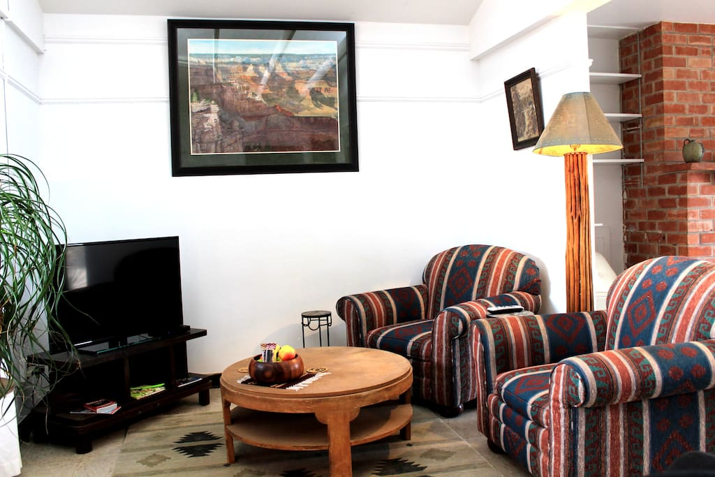 Living room sitting area of guest house with the TV on the left.