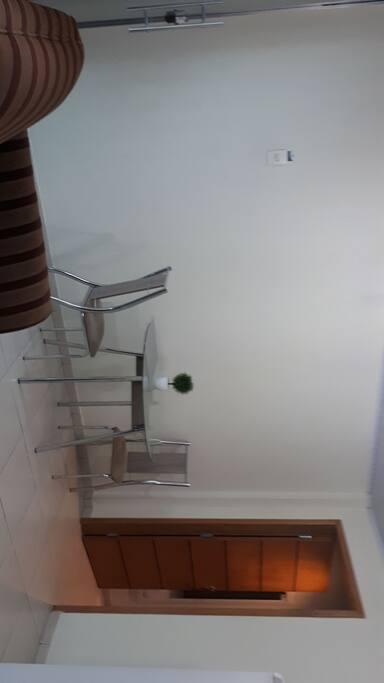 Mesa com tampo de vidro com duas cadeiras e um jarro de planta artificial.  Parte do braço do sofá.