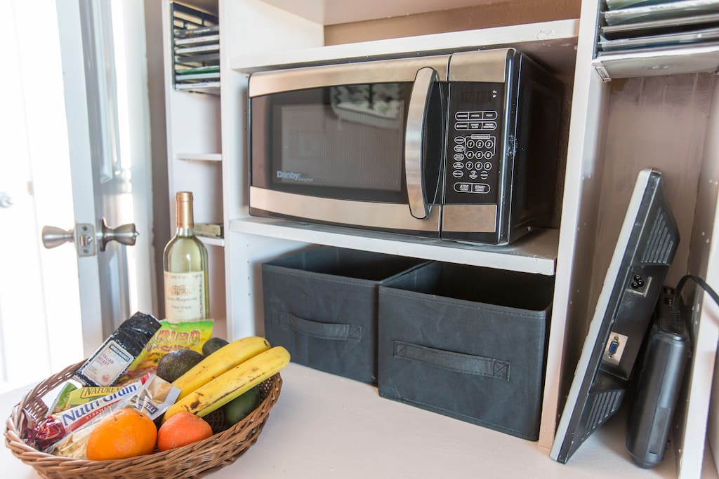 There is a microwave, refrigerator, toaster oven, juicer and assorted small kitchen appliances in the room.
