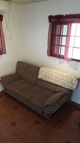 """Futon in the TV room with 32"""" flat screen TV and DVD player."""