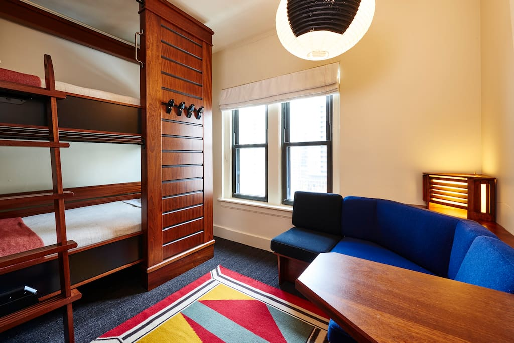 Each room has a small seating area and each bunk features a power outlet, reading lamp, and privacy curtain.