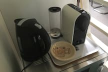 Nespresso coffee machine and water boiler on top of the microwave