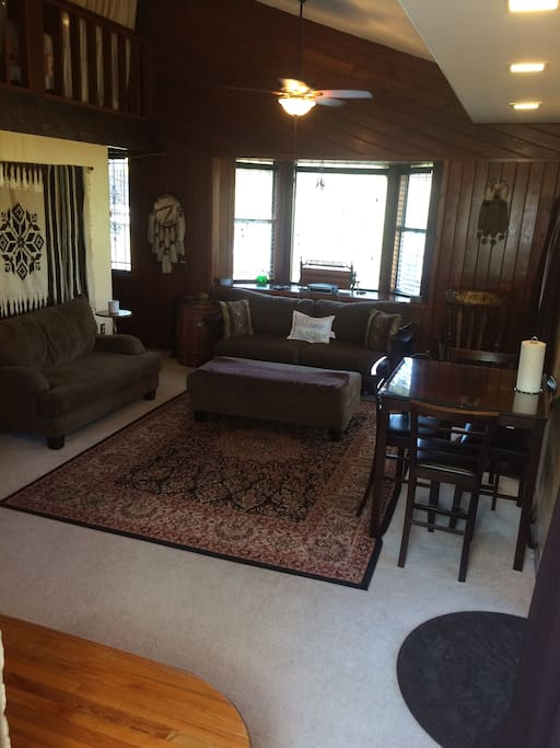 View from guests front entrance door into living room. Loft is at top left with a queen bed. The couch also converts to a queen bed.