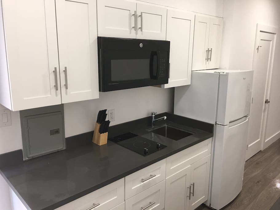 Kitchen with electric stove, microwave and refigerator