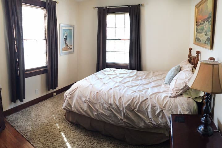 Master bedroom with queen bed and smart TV.