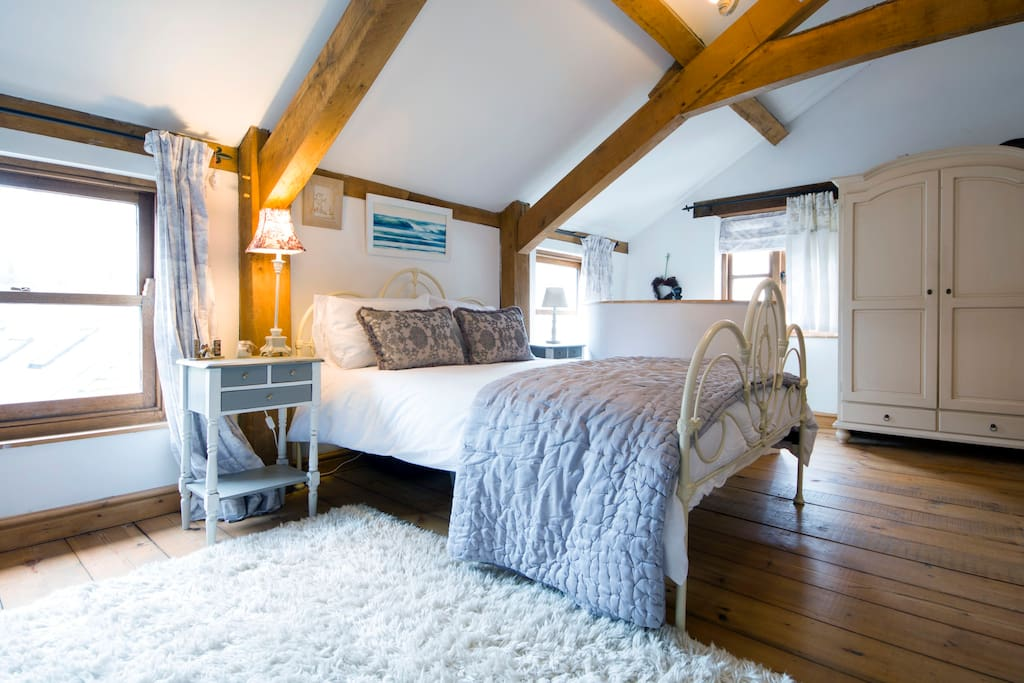 Very spacious light and airy main bedroom , exposed oak beams and wooden flooring .