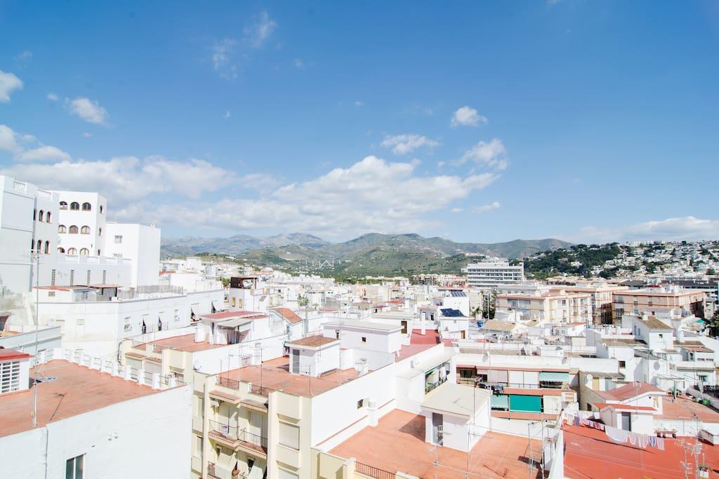 la terraza tiene unas vistas bonitas del casco antiguo y los montes