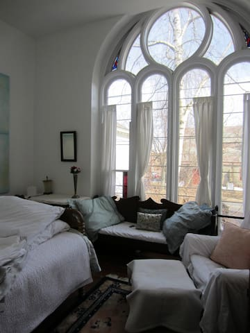 The chapel bedroom overlooking the courtyard has a double bed, settee, armchair, armoire & writing desk.