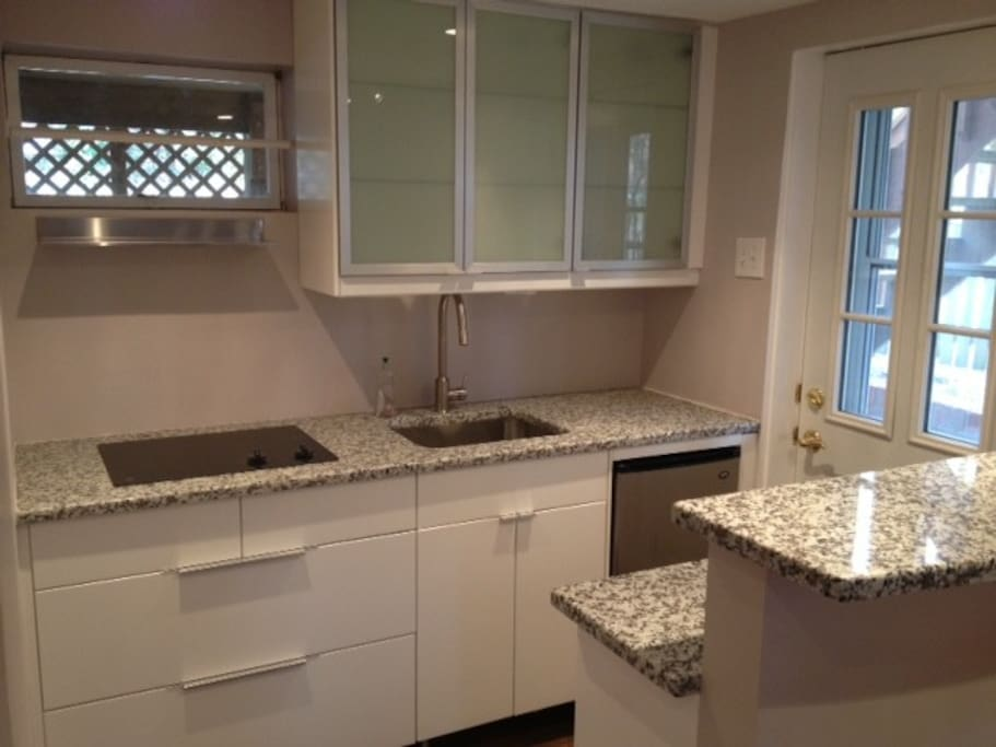 Granite counters, breakfast bar, glass cooktop, no detail spared.