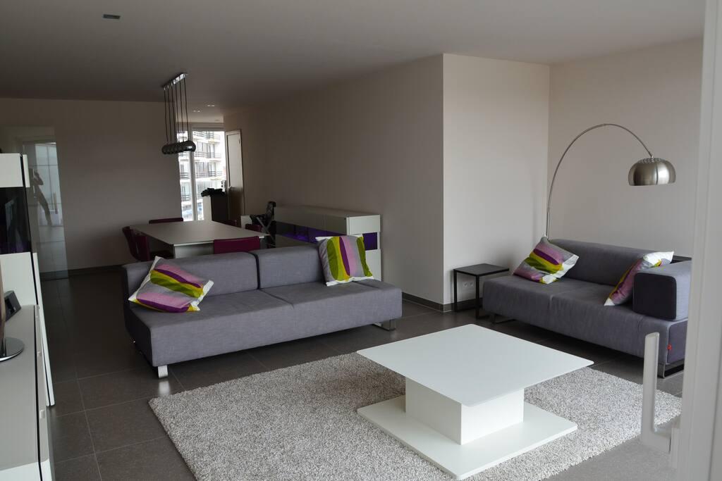 Ruime woonkamer met zithoek, eettafel en open keuken