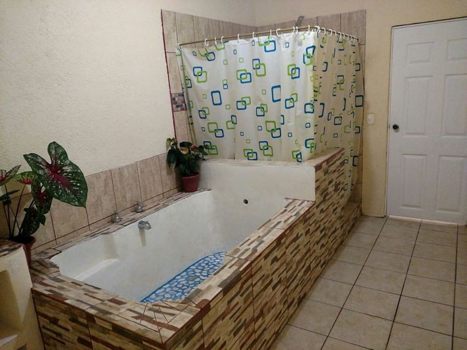 The bathroom with full tub and two-person shower