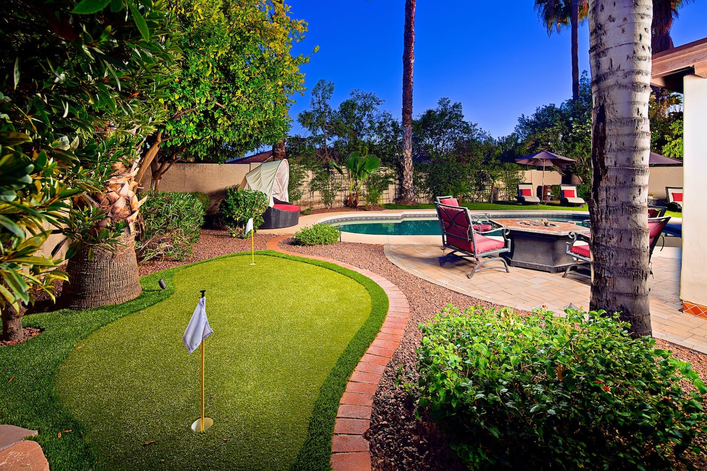 Relax in your private backyard with heated pool, fire pit, and putting green.