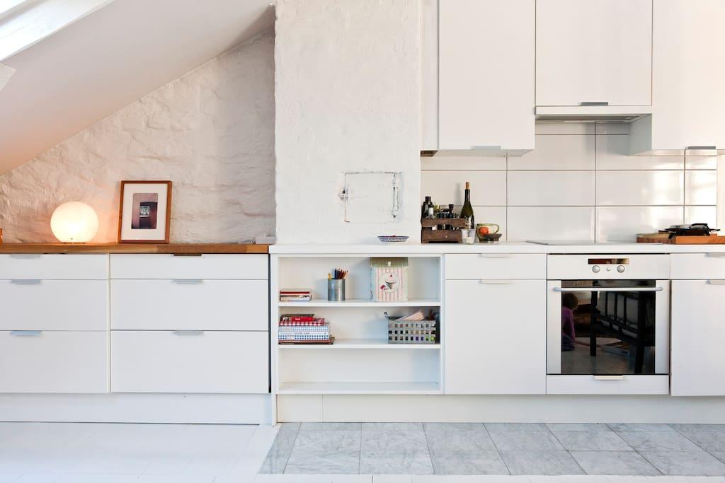 Stue og kjøkken i ett, med pen og praktisk kjøkkeninnredning.