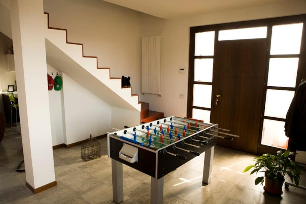 Entrance door, tablesoccer and the stairs that take you to the bedroom.