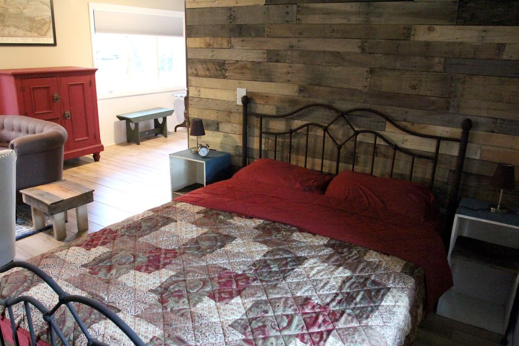 Queen sized bed. Barn wood accent wall. Repurposed antique dovetail boxes as nightstands.