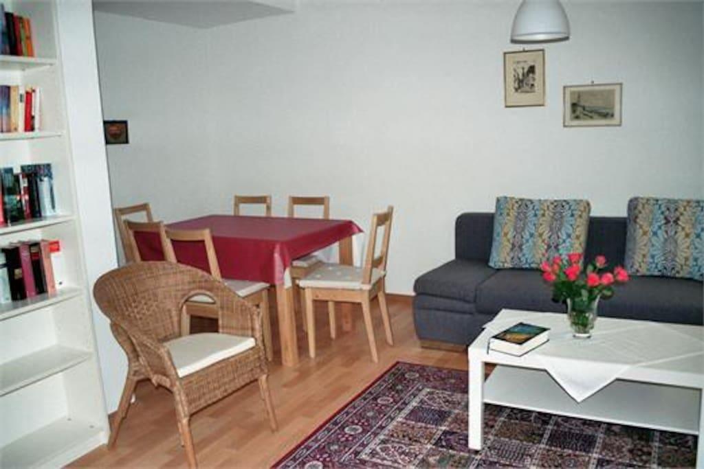 Wohnzimmer mit Blick auf Garten und Tisch