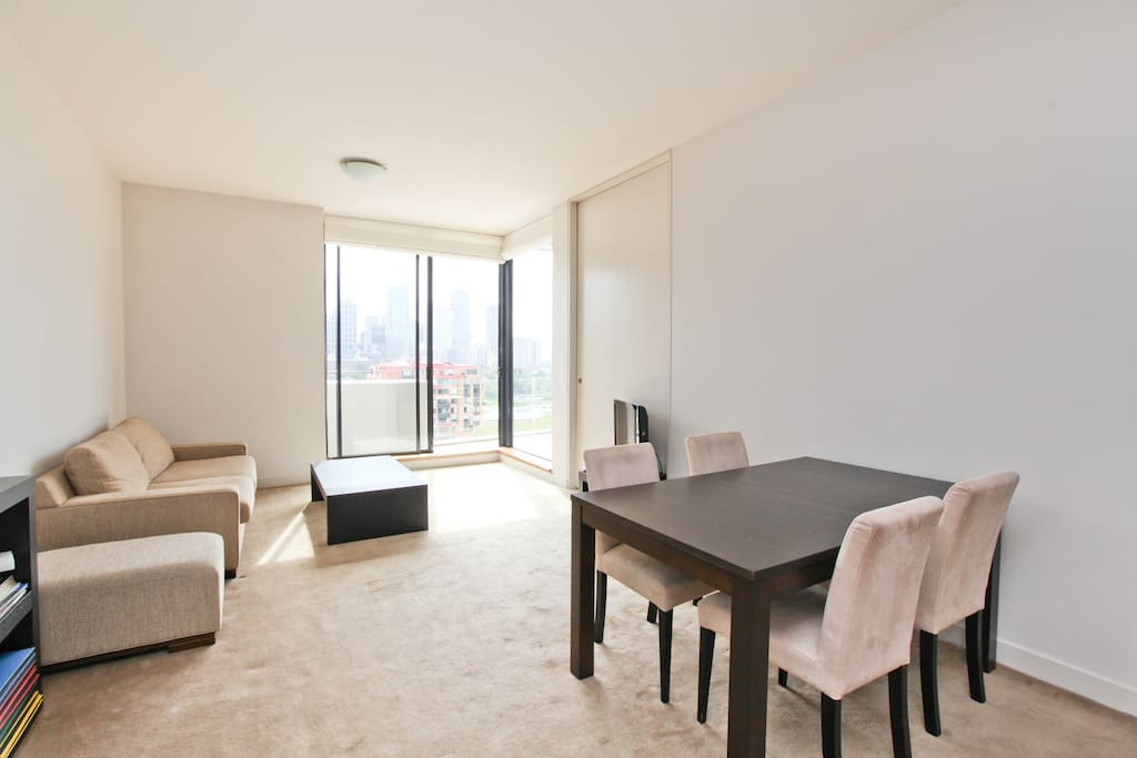 Living room with dining area with sliding glass door facing the city