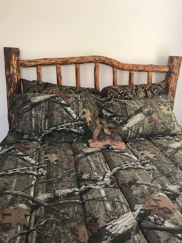 Amish queen log bed with a fabulous new foam mattress in hunting decor