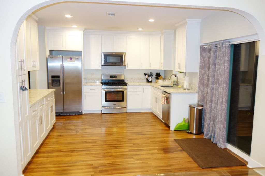 Open concept kitchen with stainless steel appliances, including gas stove and dishwasher.